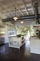 Free-standing counter in open-plan, country-house-style kitchen with ventilation duct between pendant lamps hanging from wooden ceiling