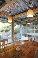 White china dish on wooden table in front of glass wall with view of garden below corrugated metal ceiling