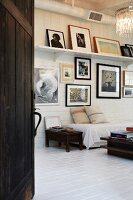 Couch with white throw below gallery of framed pictures in rustic interior