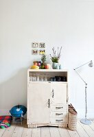 Crockery in white, half-height cabinet next to barbecue and standard lamp