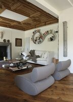 Designer easy chairs in lounge area with open fireplace, coffered wooden ceiling and curved bookshelf in background