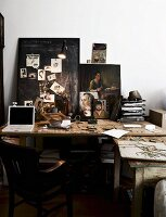 Rustic office area with studio character; laptop on wooden table, photographs stuck on blackboard and various paintings leaning against wall