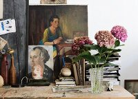 Pink hydrangeas in crystal vase on wooden worksurface in front on paintings leaning against wall in artistic, nostalgic setting