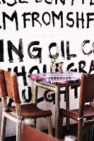Rustic bistro table and chairs made of welded pipes with leather covers in front of wall artistically decorated with black lettering