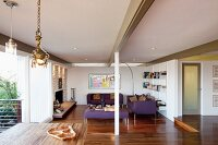 Open-plan, modern interior with exposed roof beams and purple sofa set in lounge area