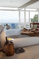Box spring bed with fur blanket in modern bedroom with panoramic view