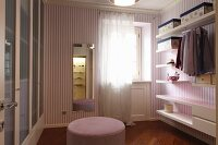 Dressing room with white shelves and clothes racks on wall, purple and white striped wallpaper and pink pouffe in middle