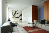 Grey, modern sofa set; dining area next to partition cupboards in open-plan interior