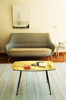 Pastel-striped rug, fifties-style table and sofa and modern artwork on wall