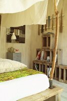 Detail of bed with unfinished branch used as support for fabric canopy; stack of heavy wooden crates in background