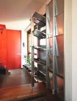 Metal cabinet with fold-down compartments next to windowsill; red door in background