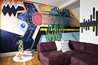 Bold, stylish mural behind aubergine corner sofa and vintage side table