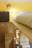 Fitted furnishings made from multiplex wood boards with loft bed and integrated bookcase