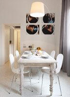 Photographs above dining area with laminated wood chairs, white-painted, country-house table and arc lamp
