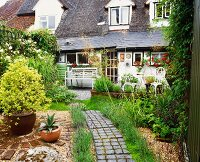 Paved path in idyllic summer garden; white bench in background in front of simple, English country house