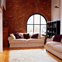 Exposed brickwork and hardwood floors contrasting with soft white sofas and fluffy rug