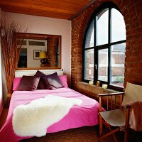 Exposed brick wall creating textural accent in bedroom