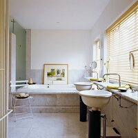 Pedestal sinks below window with closed louver blinds and marble-clad bathtub in background