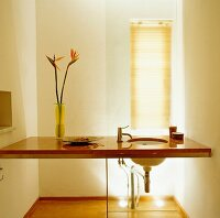 Vase of bird-of-paradise flowers on floating washstand between two walls in minimalist bathroom