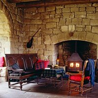 Cosy, stylish seating area with antique bench, chair and matching table in front of log burner in old fireplace in rustic stone wall