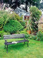 Black vintage bench on lawn in front of traditional conservatory in raised area