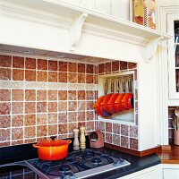 Kitchen counter with gas hob in tiled mantel hood with white, carved wooden surround