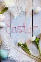Easter arrangement of eggs, feathers, flowers & 'Easter' written in wire