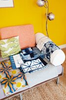 Batik fabrics on couch with cushions against yellow wall