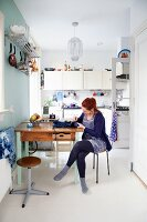 Young woman sitting at kitchen table below cooking utensils hanging from shelf on wall in front of white fitted kitchen