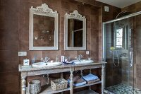 Vintage-style washstand with twin sinks and ornate mirrors next to glazed shower area