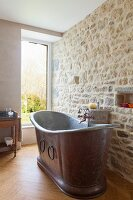 Vintage metal bathtub against stone wall in renovated bathroom with window
