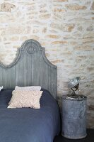 Grey-painted bed headboard next to spotlight on metal can used as bedside table against stone wall