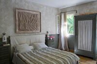 Double bed with striped bedspread and wardrobe with gathered fabric door panel in bedroom in natural shades
