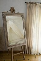 Dressing mirror in old cabinet top frame on painters' easel in Provençal bedroom