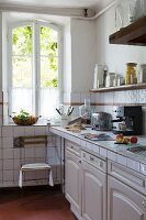 Provençal country-house kitchen with tiled worksurface and terracotta floor