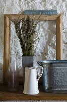Still-life arrangement of vintage vessels made from zinc, enamel and glass with bunch of dry lavender and wooden frame against roughly plastered wall