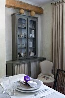 Wooden beam above grey-painted crockery cabinet with fabric panels in lower doors, upholstered chair and set table in foreground