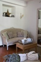 Old, stripped side table and antique couch next to full-length mirror; bunch of lavender in foreground