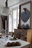 Set table below decorated wire mesh pendant lamp and ornamental heart mounted on framed mirror on top of flea-market cabinet