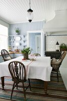 Potted strawberry and Windsor chairs in kitchen-dining room with wood-panelled walls