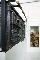 Antique kitchen stove with brass towel rail and firewood in niche in background