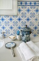 Traditional, blue and white tiles, hand mirror and ceramic pot on stone washstand counter