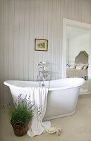 Potted lavender in front of free-standing bathtub with vintage tap fittings in ensuite bathroom