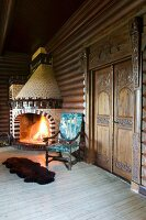 Fire in artistic, masonry, corner fireplace made from pale and brown decorative bricks in rustic, log-cabin-style interior