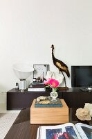 Wooden box and book on coffee table, vintage table lamp, stuffed bird and TV on sideboard in background