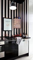 Modern kitchen counter with black and white base units against wallpaper with wide black and white stripes