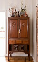 Antique Oriental cabinet decorated with collectors' items, vases and potted plants