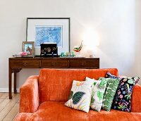 Orange sofa with patterned scatter cushions in front of table lamp on antique console table