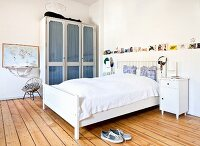 White double bed with headboard, glass-fronted cabinet and wooden floor in rustic bedroom with vintage ambiance