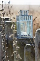 A chrome-plated metal lantern on a wooden stake